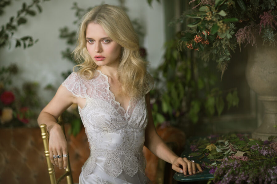 Claire Pettibone wedding dress on blonde model with tossed hair. Sitting in chair looking intense.