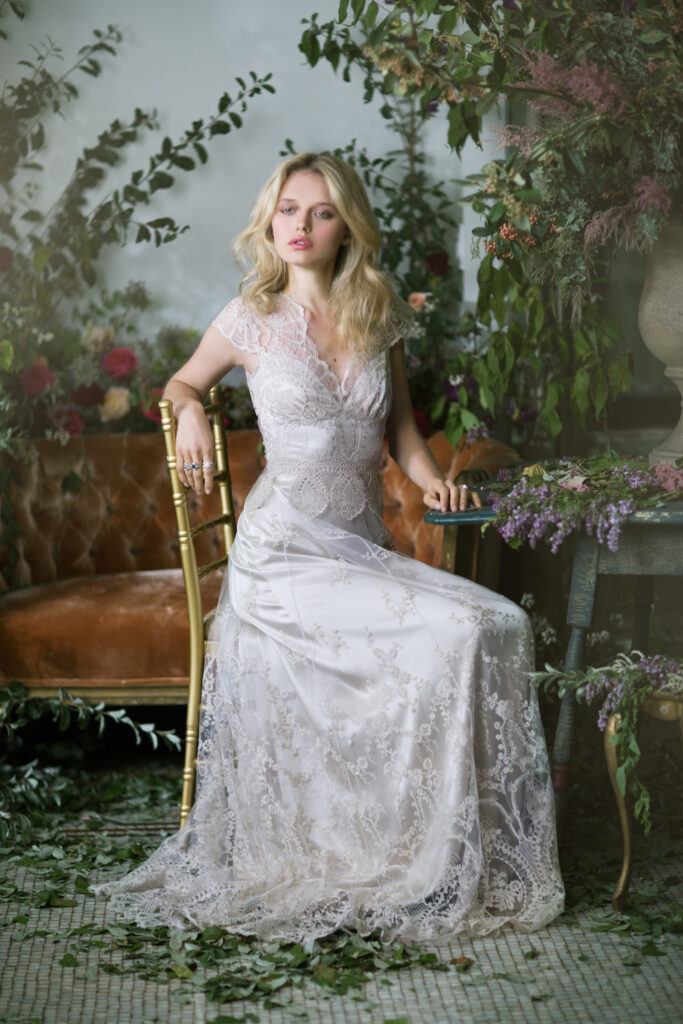 Claire Pettibone wedding dress on blonde model with tossed hair. Sitting on chair with greenery around in natural style.