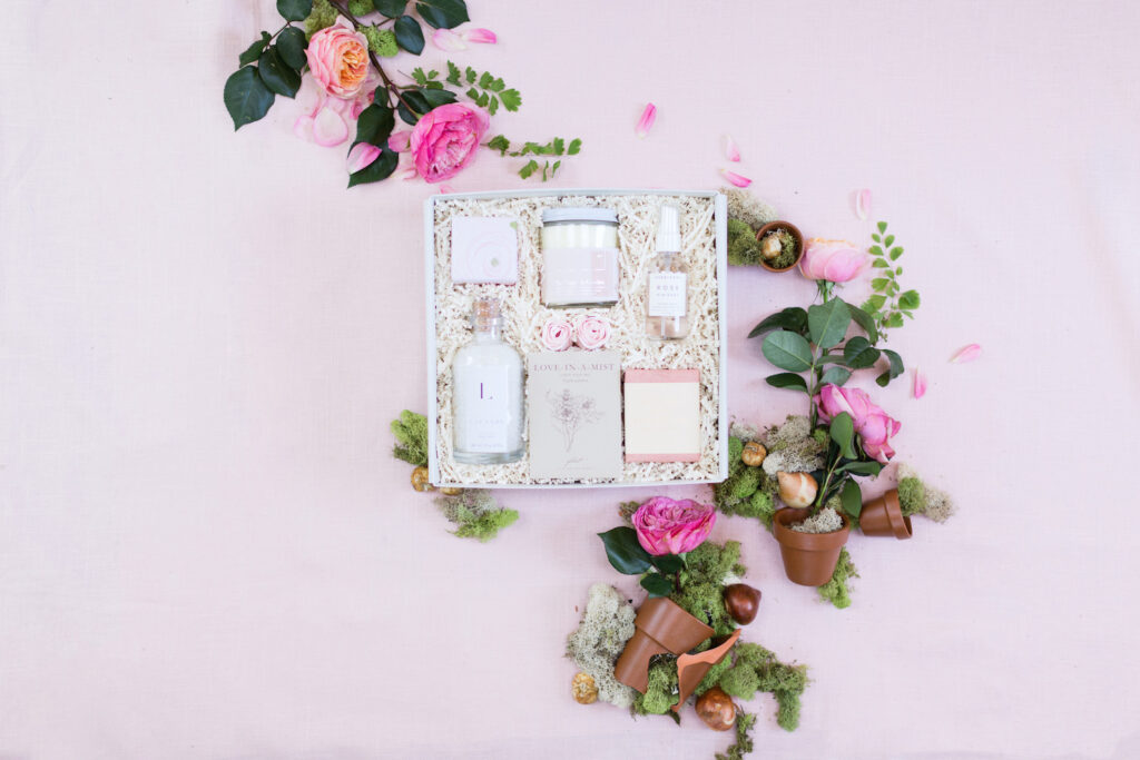 Light pink flatlay with giftbox with items. Around the box is flowers and flower pots.