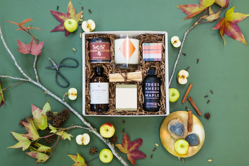 Fall flatlay with apples and leaves and a fall themed giftbox with a candle, maple, and palo santo.