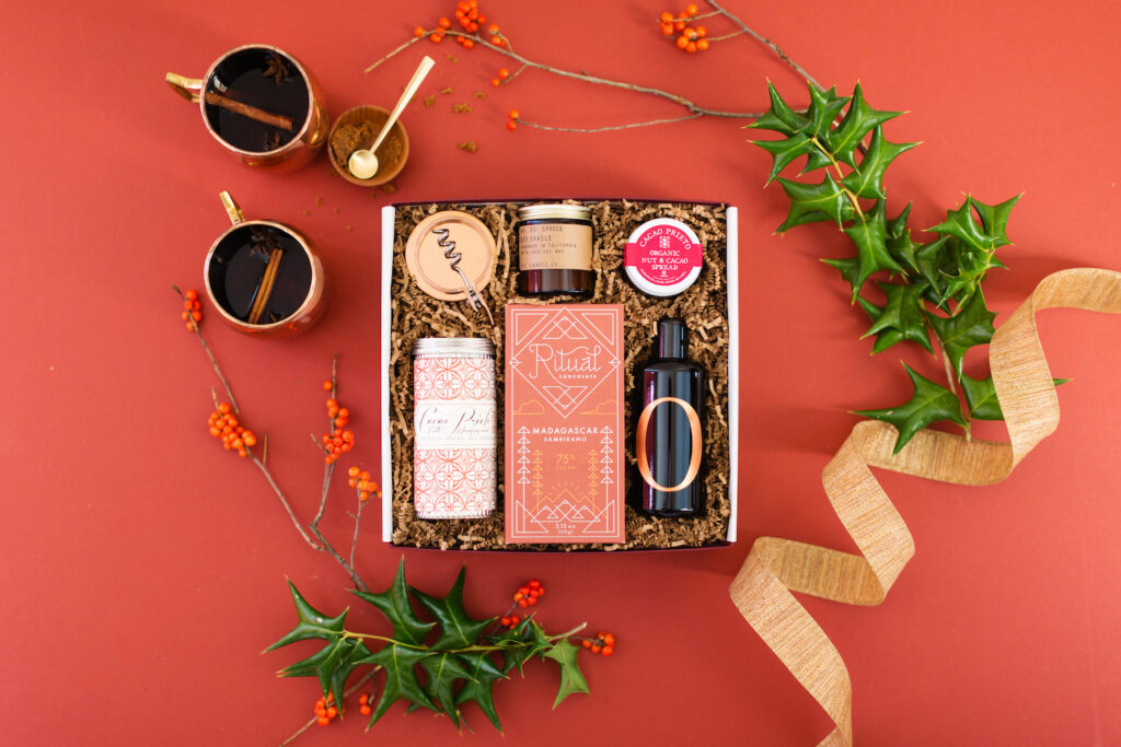 Fall giftbox with flatlay featuring spiced cider and berries. Box and cozy fall time items.